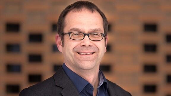Porträt von Prof. Johannes Hübner von der Martin-Luther-Universität Halle-Wittenberg vor einer orang-bräunlichen Ziegelwand. Er trägt eine schwarze Brille, einen schwarzen Anzug und ein dunkelblaues Hemd.