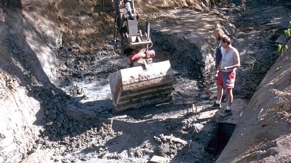 Zwei Männer vor einer Baggerschafel im Loch einer Ausgrabung in Schweden