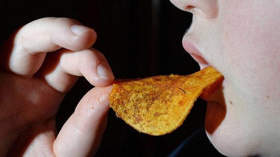 Ein Junge isst Kartoffelchips