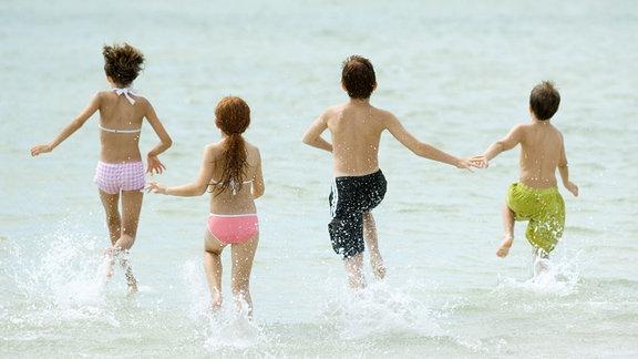 Kinder rennen ins Meer.