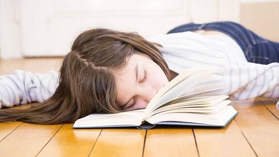 Ein Mädchen liegt auf einem Buch und schläft.