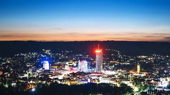 Skyline von Jena in der Dämmerung: Beleuchtete Stadt, mehrere Hochhäuser, im Hintergrund dunkle Anhöhe, dahinter Lichtstreifen am Horizont und dunkelblauer Abendhimmel.