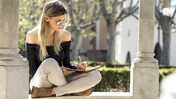 Eine junge Frau mit Sonnenbrille sitzt auf einer Bank und schreibt in ein Heft