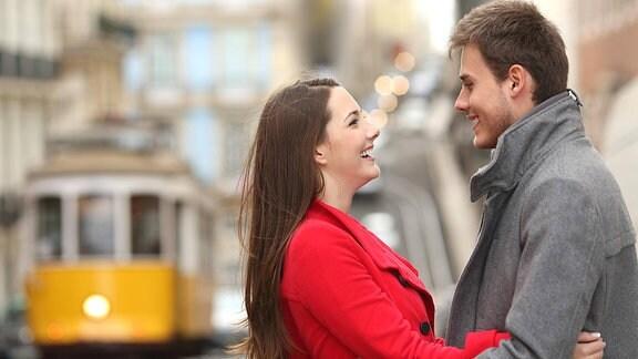 Eine junge Frau und ein junger Mann lachen sich an