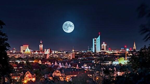 Skyline von Leipzig bei Nacht mit vielen beleuchteten Häusern und einigen Hochhäusern. Darüber Vollmond als Fotomontage.