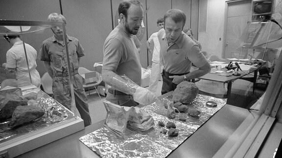 Crew-Mitglieder der Apollo-14-Mission betrachten ausgelegtes Mondgestein in einem Labor (Schwarz-weiß-Bild).