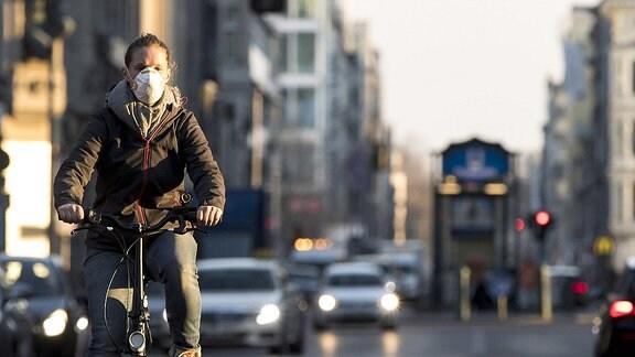 Eine Radfahrerin mit Mundschutz
