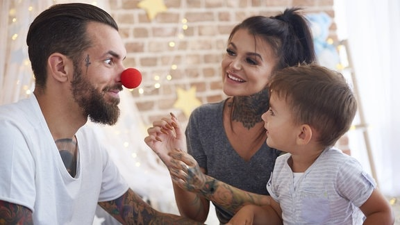 Mann mit Clownsnase, Frau und Kind