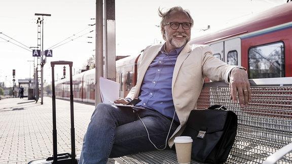 Ein Mann sitzt auf einer Bank und hat Kopfhörer im Ohr.