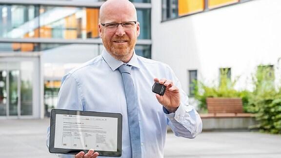 Ein Mann hält ein Tablet einen Tracker - Dr. Stefan Moritz von der Universitätsmedizin Halle/S.