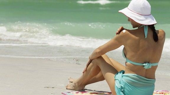 Frau am Strand cremt sich ein