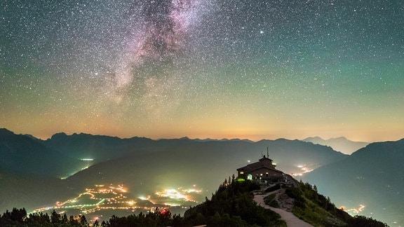 Eine Berghütte, ein hell erleuchtes Dorf im Tal, darüber der Sternenhimmel