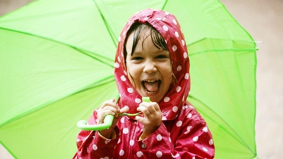 Lachendes Kind in rotem Anorak mit weißen Punkter und grünem Regenschirm im Regen.