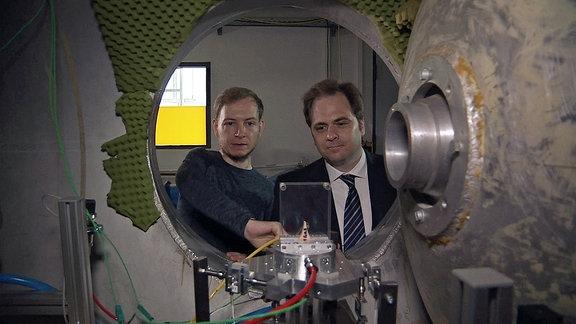 Zwei Männer betrachten eine Apparatur hintter einer Luke.