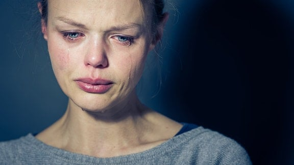 Eine junge Frau weint.