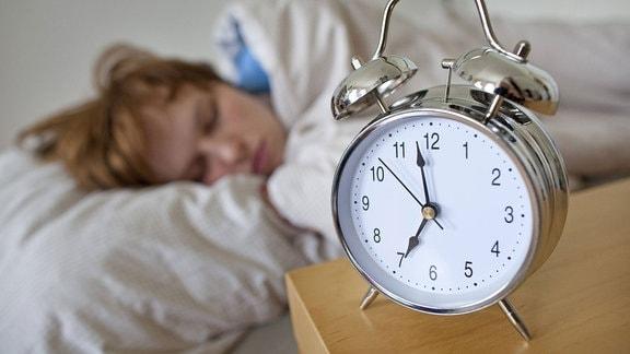 Hinter einem Wecker liegt eine schlafende Frau in einem Bett