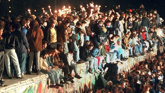 Jubelnde Menschen sitzen mit Wunderkerzen auf der Berliner Mauer am 11.11.1989.
