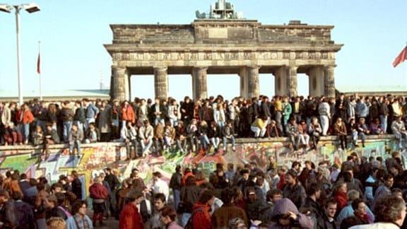 Unzählige Menschen am 10.11.1989 auf und vor der Mauer am Brandenburger Tor in Berlin