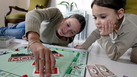 Zwei Mädchen spielen Monopoly.